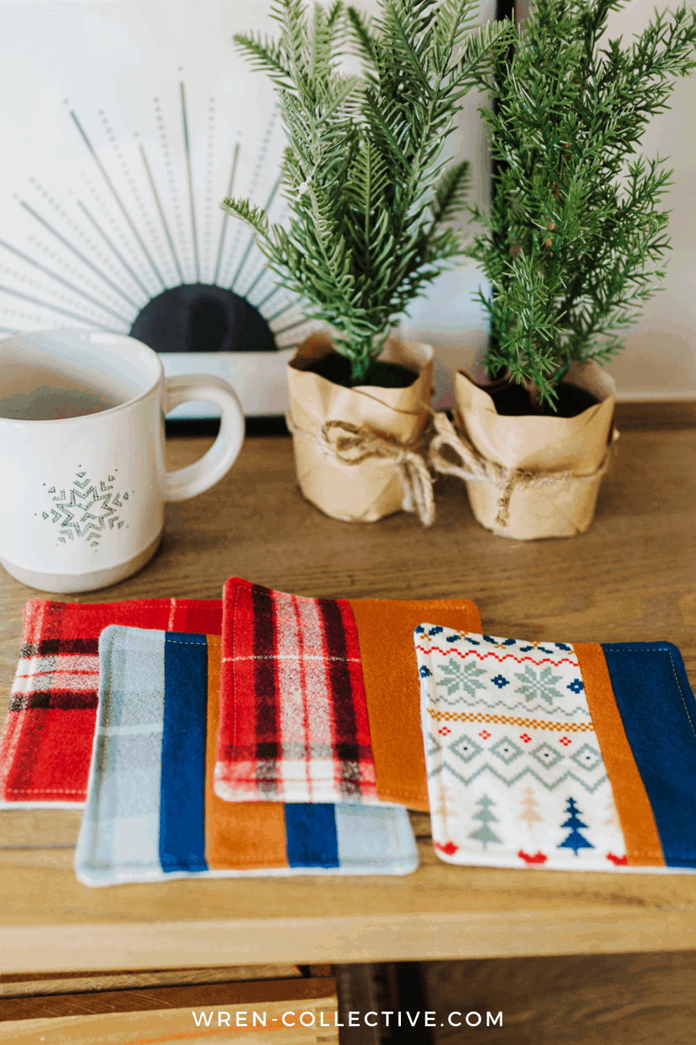 Coasters are the perfect fabric scrap project. All four coasters are laid out in front of a winter ceramic mug and two artificial evergreen trees. Free coaster tutorial from wren-collective.com