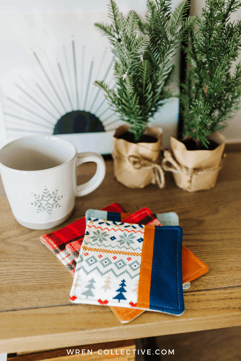 Four fabric scrap project coasters sitting on a shelf in front of a ceramic mug. This free tutorial is from Rachel of Wren Collective.