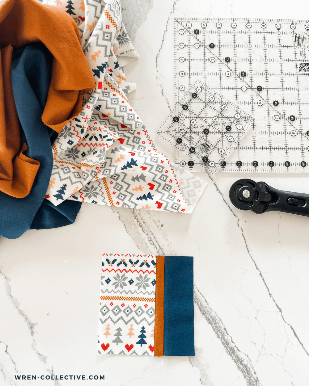 A pieced coaster top sits in front of a rotary cutter, flannel scraps, and square rulers. This fabric scrap project is a free tutorial from Rachel of Wren Collective.