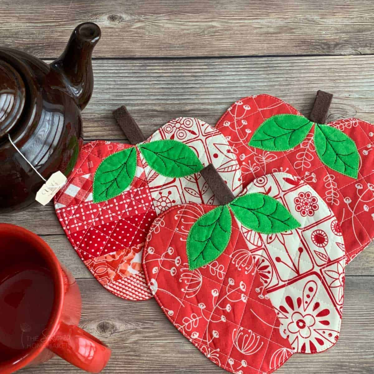 Three fabric coasters shaped like apples. This fall sewing project is pictured with a tea kettle and cup of tea.