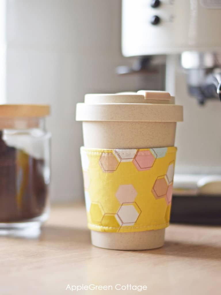 A coffee cozy on a mug of coffee, sitting in front of a coffee machine. Fall sewing projects roundup post from Rachel of Wren Collective